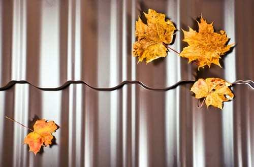 Fragment of a new metal roof with yellow leaves on it