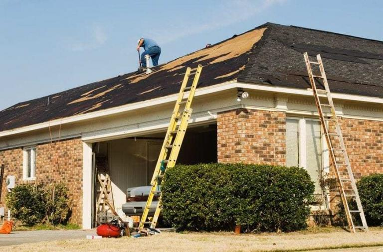 Roofer repairing the roof of a brick house in the suburbs.