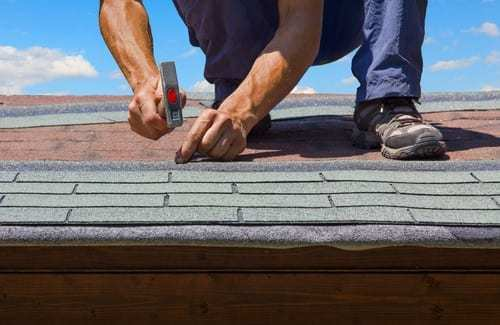 roofer applying shingles to roof