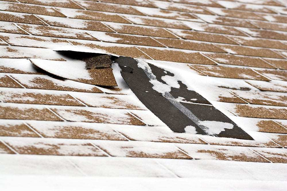 Roof with shingles that have curled up, snow on roof