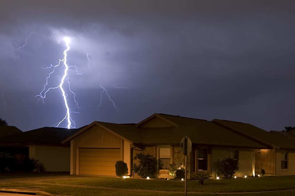 Lightning bolt striking above residential roof