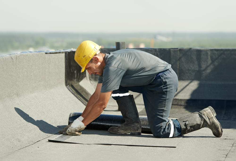 Roofer applying roofing felt to flat roof