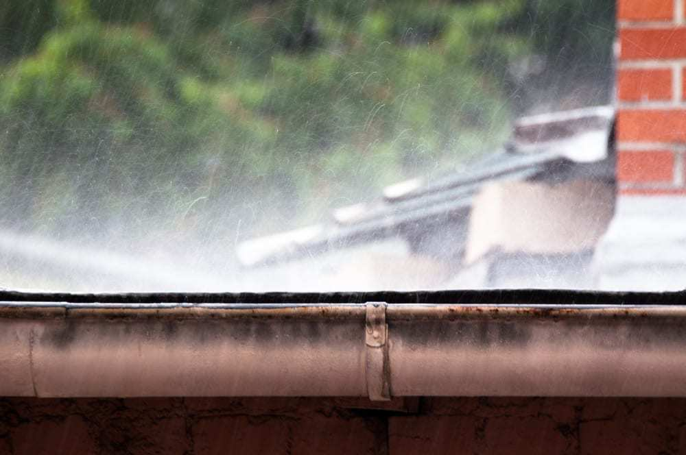 Heavy rain pounding the edge of a roof, gutters