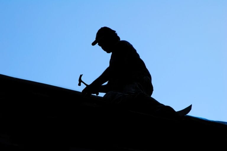 Silhouette of roofer, blue sky