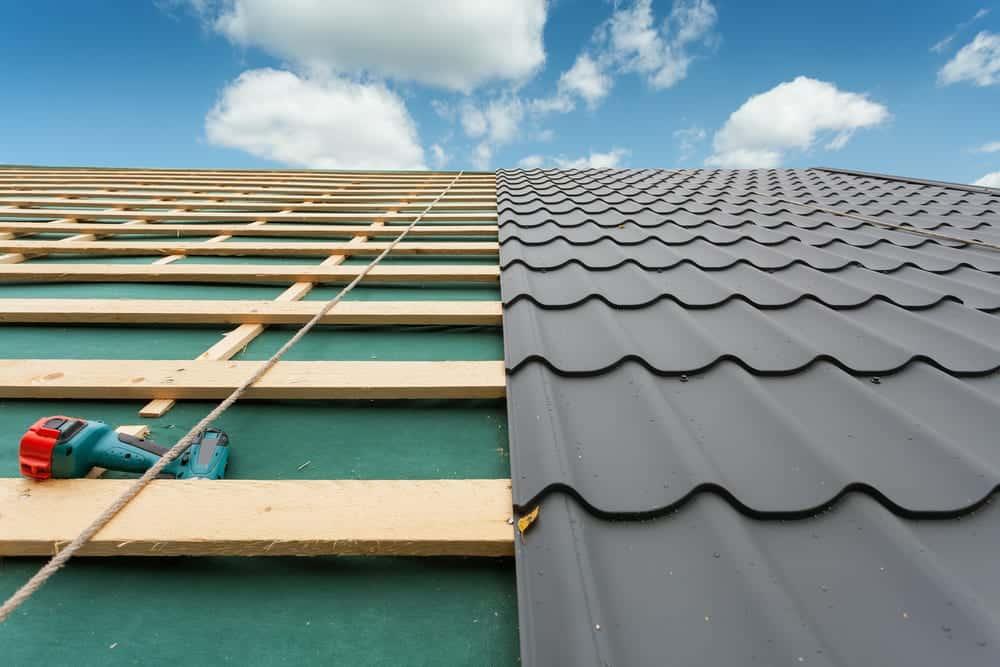 Roof under construction, half metal tile, half unfinished
