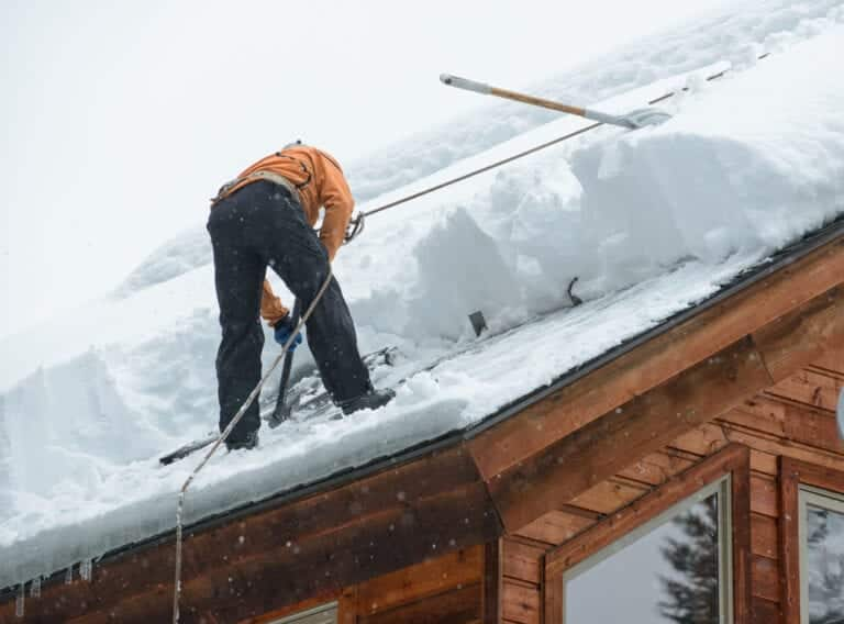 Mean on roof clearing ice dam