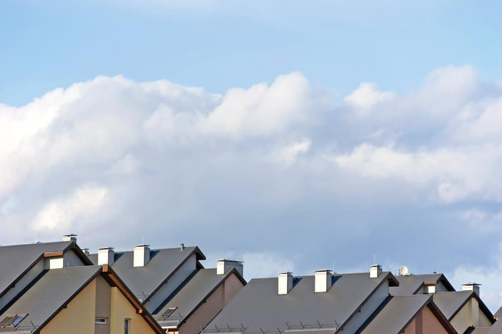 Cropped image of roofs of suburban houses and cloudy blue sky