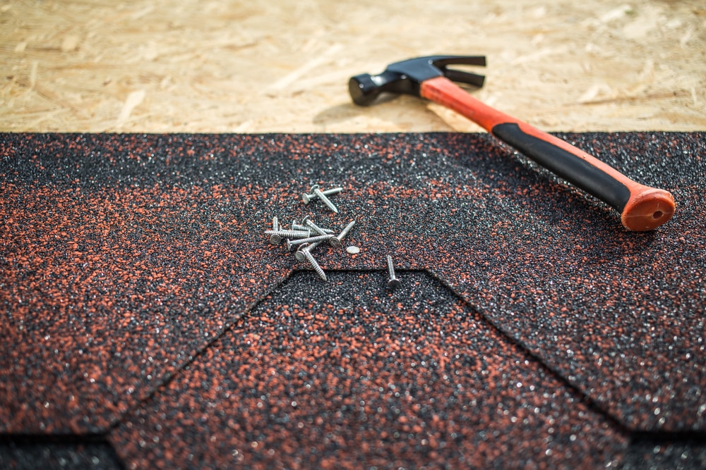 hammer and nails on partially constructed asphalt roof